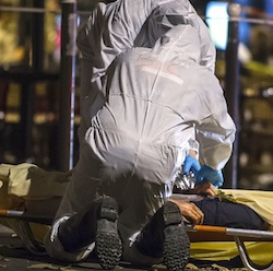 Investigating police officers inspect the lifeless body of a victim of a shooting attack outside the Bataclan concert hall in Paris, France, Saturday, Nov. 14, 2015. Well over 100 people were killed in Paris on Friday night in a series of shooting, explosions. French President Francois Hollande declared a state of emergency and announced that he was closing the country's borders. (AP Photo/Kamil Zihnioglu)