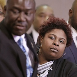 Samaria Rice, center, the mother of Tamir Rice, a 12-year-old boy fatally shot by a Cleveland police officer, watches the video of Tamir's shooting during a news-conference in Cleveland, March 2015. Attorney Benjamin Crump, left, and attorneys Walter Madison, right, watch. Attorneys for the family of Tamir Rice have asked a prosecutor to allow their use-of-force experts to testify before the grand jury. (AP Photo/Tony Dejak, File)