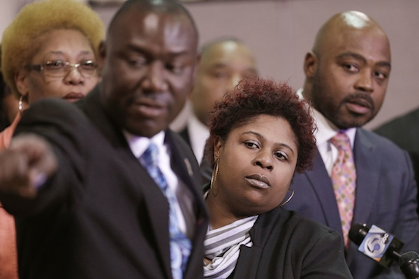 Samaria Rice, center, the mother of Tamir Rice, a 12-year-old boy fatally shot by a Cleveland police officer, watches the video of Tamir's shooting during a news-conference in Cleveland. Attorney Benjamin Crump, left, and attorneys Walter Madison, right, watch. Attorneys for the family of Tamir Rice have asked a prosecutor to allow their use-of-force experts to testify before the grand jury. (AP Photo/Tony Dejak, File)