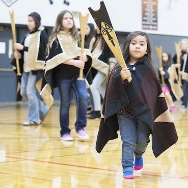 ayde Diaz and other members of the Canoe family, perform a dance during the Grand Ronde tribal flag posting ceremony, Nov. 16, 2015, at the high school gym in Willamina, Ore. (Marcus Larson/News-Register via AP)
