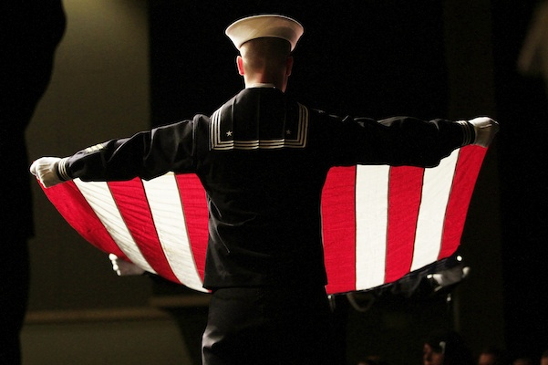 CS2 Matthew Oberg with the Navy Operation Support Center performs a flag fold done at military funerals during the Veterans Day observance Thursday, Nov. 5, 2015, at Kettle Moraine Lutheran High School in Jackson, Wis. (John Ehlke/West Bend Daily News via AP)