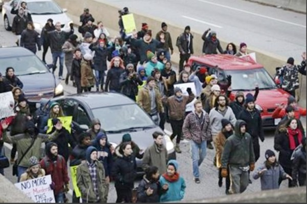 Protesters block cars on the freeway during a protest over the police shooting of Tamir Rice in Cleveland, Nov. 25, 2014. A white Cleveland police officer was justified in fatally shooting a black 12-year-old boy holding a pellet gun moments after pulling up beside him, according to two outside reviews conducted at the request of the prosecutor investigating the death. The reports were released Saturday, Oct. 10, night by the Cuyahoga County Prosecutor's Office, which asked for the outside reviews as it presents evidence to a grand jury that will ultimately determine whether Timothy Loehmann will be charged in the death of Rice. (AP Photo/Tony Dejak, File)