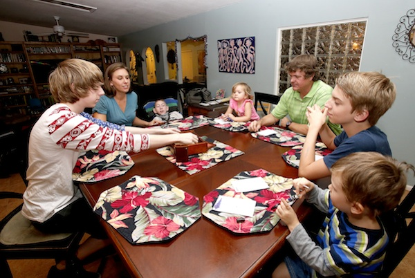 "In this Wednesday, Sept. 30, 2015 photo, from left, Jo Armstrong, Julie Armstrong, Skylar Armstrong, Amelia Anderson, Nathan Anderson, Westley Armstrong and Dean Anderson sit together for a game at their home in Tucson, Ariz. At 42 with a blended family of five, Nathan Anderson runs an acupuncture clinic with his wife, Julie, also an acupuncturist. Combined, their monthly student loans bills approach $1,700. ""More than we spend on groceries and kind of like having a second mortgage,"" Nathan said. (AP Photo/Rick Scuteri)"