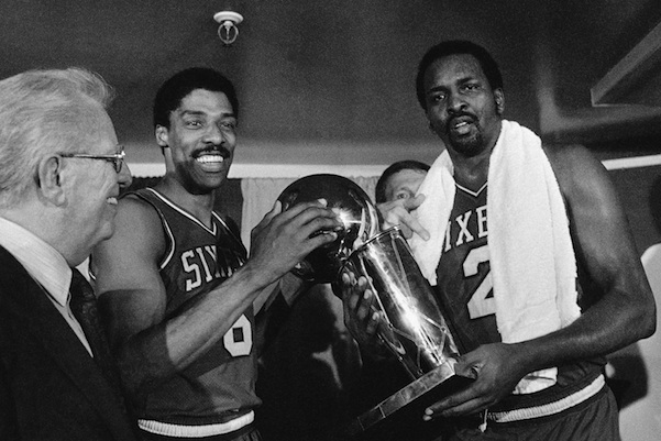 Philadelphia 76ers Julius Erving, left, and Moses Malone, right, hold the NBA Championship trophy after defeating the Los Angeles Lakers in Los Angeles Tuesday, May 31, 1983. Malone, a three-time NBA MVP and one of basketball's most ferocious rebounders, died Sunday, Sept. 13, 2015, according to a The Philadelphia 76ers statement. He was 60. (AP Photo/File)