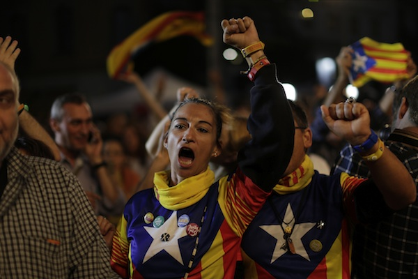 Catalonian independence supporters react in Barcelona, Spain, Sunday Sept. 27, 2015. Voters in Catalonia participated in an election Sunday that could propel the northeastern region toward independence from the rest of Spain or quell secessionism for years. Secessionists have long pushed for an independence referendum, but Spain's central government has not allowed one, arguing it would be unconstitutional because only it can call such a vote. (AP Photo/Emilio Morenatti)