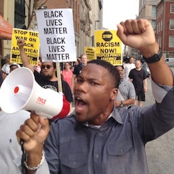 "Pastor Westley West, from Faith Empowered Ministries, leads protesters as they march towards Pratt Street and the Inner Harbor, Wednesday, Sept. 2, 2015, in Baltimore, as the first court hearing was set to begin in the case of six police officers criminally charged in the death of Freddie Gray. Six police officers face charges that range from second-degree assault, a misdemeanor, to second-degree ""depraved-heart"" murder. (Lloyd Fox/The Baltimore Sun via AP"