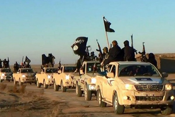 "Militants of the Islamic State group hold up their weapons and wave its flags on their vehicles in a convoy on a road leading to Iraq, while riding in Raqqa city in Syria. When world leaders convene for the U.N. General Assembly debate Monday, Sept. 28, 2015, it will be a year since the U.S. president declared the formation of an international coalition to ""degrade and ultimately destroy"" the Islamic State group. Despite billions of dollars spent and thousands of airstrikes, the campaign appears to have made little impact. (Militant website via AP, File)"