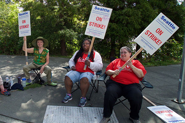 Women in chairs holding picket signs.