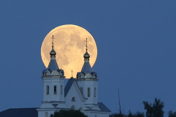 A perigee moon, also known as a super moon, rises above the Orthodox Church in the town of Novogrudok, 150 kilometers (93 miles) west of the capital Minsk, Belarus, Saturday, Aug. 29, 2015. The supermoon happens when moon is full and makes it closest approach to Earth in her orbit. (AP Photo/Sergei Grits)