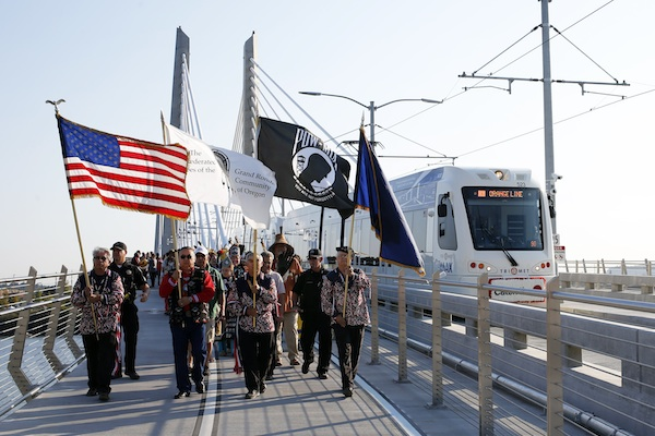 An honor guard from the Confederated Tribes of the Grand Rond lead a procession before the kickoff for the newly opened Tilikum Crossing, a unique bridge, in Portland, Ore., Saturday, Sept. 12, 2015. The bridge is just the latest example of Portland's green, bike friendly persona. (AP Photo/Timothy J. Gonzalez)