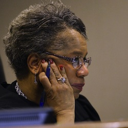 Genesee District Court Judge Tracy Collier-Nix looks on as Jeff Seipenko, Special Agent at State of Michigan Attorney General, speaks on Wednesday, April 20, 2016 at the Floyd J. McCree Courts & Human Services Center in Flint, Mich. Two state regulators and a Flint employee were charged Wednesday with evidence tampering and several other felony and misdemeanor counts related to the Michigan city's lead-tainted water crisis. (Rachel Woolf /The Flint Journal-MLive.com via AP)