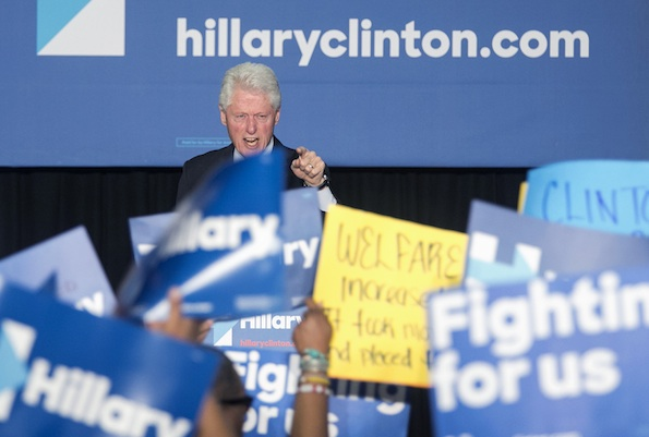 "Former President Bill Clinton has a heated exchange with a protester during a rally for Democratic presidential candidate Hillary Clinton, Thursday April 7, 2016, in Philadelphia. Bill Clinton was interrupted by people in the crowd holding signs reading ""Clinton crime bill destroyed our communities"" and ""Welfare reform increased poverty."" (Ed Hille/The Philadelphia Inquirer via AP)"