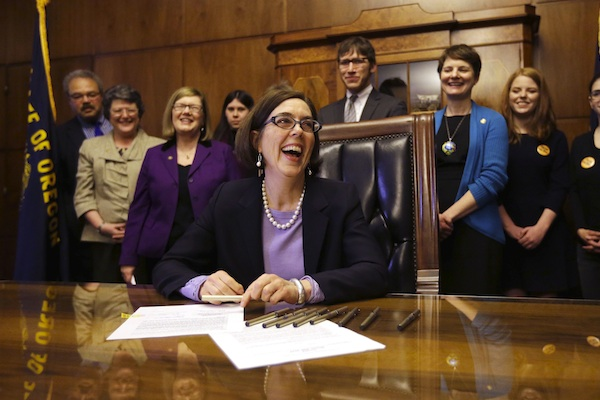Oregon Gov. Kate Brown smiles after signing an automatic voter registration bill in Salem, Ore. on March 15, 2016. After months of increasing public pressure to take a position, Brown on Thursday, Aug. 4, 2016, endorsed labor unions' November ballot proposal that would impose the largest tax hike on corporations in Oregon history. (AP Photo/Don Ryan, file) Summary