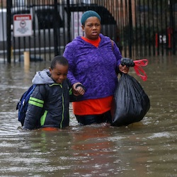 Residents wade through floodwaters from heavy rains in the Chateau Wein Apartments in Baton Rouge, La., Friday, Aug. 12, 2016. Heavy downpours pounded parts of the central U.S. Gulf Coast on Friday, forcing the rescue of dozens of people stranded in homes by waist-high water and leaving one man dead who became trapped by floodwaters. (AP Photo/Gerald Herbert)