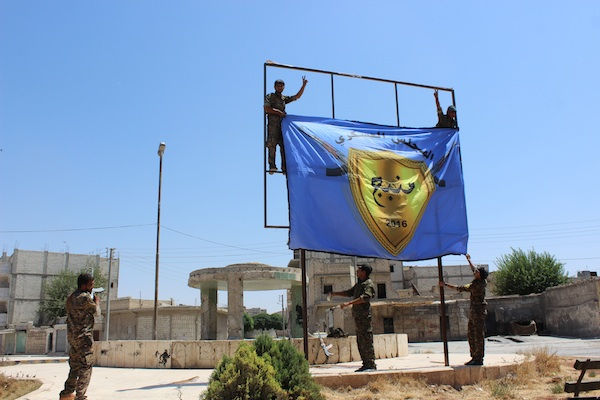 Kurdish-led Syria Democratic Forces raise their flag in the center of the town of Manbij after driving Islamic State militants out of the area, in Aleppo province, Syria. Syrian Kurdish officials and an activist group say U.S.-backed fighters have seized a key Islamic State stronghold in northern Syria after two months of heavy fighting and freed hundreds of civilians the extremists had used as human shields. (ANHA via AP)