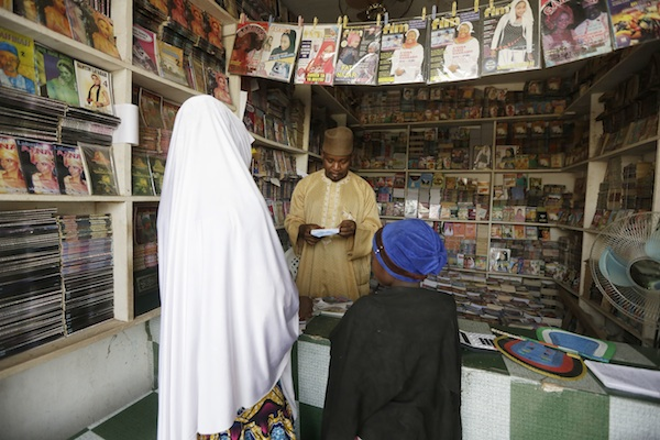 Suleiman Maharazu, centre, the owner of Maharazu Bookshop, sells books to young girls in his shop in Kano, Nigeria. In the local market stalls are signs of a feminist revolution with piles of poorly printed books by women, as part of a flourishing literary movement centered in the ancient city of Kano, that advocate against conservative Muslim traditions such as child marriage and quick divorces. dozens of young women are rebelling through romance novels, many hand-written in the Hausa language, and the romances now run into thousands of titles. (AP Photo/Sunday Alamba)