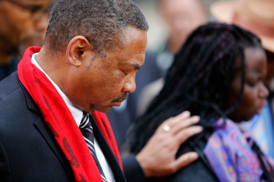 Pastor Thomas Dixon, left, prays during a prayer vigil in front of the Charleston County Courthouse