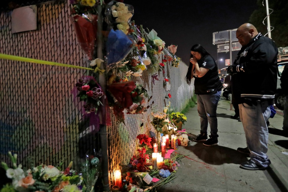 Sol Rodriguez, center, and Aaron Torres visit a shrine for the victims of a warehouse fire near the site in Oakland, Calif.