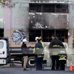 Emergency crews work in front of the site of a warehouse fire in Oakland, Calif.