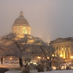 Thursday, Dec. 8, 2016, the Washington Capitol is seen at sunset as snow falls in Olympia, Wash. Snow fell across the Pacific Northwest as the first winter storm of the season hit the region. (AP Photo/Rachel La Corte)