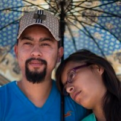 Hugo Ballin and wife Uviridiana Soto sit near the border fence between New Mexico and Mexico, Monday, Feb. 15, 2016, in Juarez. The couple went to go see Ballin's uncle, who he hasn't seen in 8 years. Hundreds of immigrant families and border residents from Southern New Mexico, Juarez and El Paso met at a border fence in the outskirts of town during a Border Network for Human Rights event. (AP Photo/Ivan Pierre Aguirre)