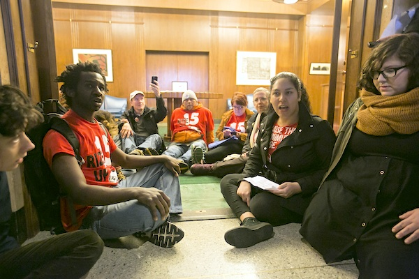 Alyssa Pagan, second from right, leads a chant against high rents and low wages as a group of protestors sit in the doorway of the governor's office at the Capitol on Thursday, Feb. 18, 2016 in Salem, Ore. The Oregon House of Representatives on Thursday approved landmark legislation that not only raises the state's minimum wage for all workers to the highest level in the country, but does so through an unprecedented three-tiered system that sets different rates by geographic region. (Molly J. Smith/Statesman-Journal via AP)