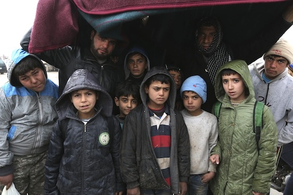 Syrians try to protect themselves from rain near the Bab al-Salam border crossing with Turkey, in Syria, Saturday, Feb. 6, 2016. Some thousands of Syrians have rushed toward the Turkish border, fleeing fierce Syrian government offensives and intense Russian airstrikes. Turkey has promised humanitarian help for the displaced civilians, including food and shelter, but it did not say whether it would let them cross into the country. (AP Photo/Bunyamin Aygun)