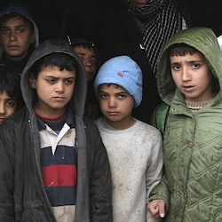 Cold, hungry, fleeing from violence, these Syrian boys try to protect themselves from rain near the Bab al-Salam border crossing with Turkey, in Syria, Saturday, Feb. 6, 2016. Some thousands of Syrians have rushed toward the Turkish border, fleeing fierce Syrian government offensives and intense Russian airstrikes. Turkey has promised humanitarian help for the displaced civilians, including food and shelter, but it did not say whether it would let them cross into the country. (AP Photo/Bunyamin Aygun)