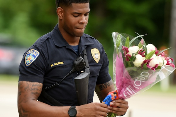 Baton Rouge Police Department Officer Markell Morris holds a bouquet of flowers and a Superman action figure that a citizen left at the Our Lady of the Lake Hospital where the police officers were brought this morning, Sunday, July 17, 2016. Multiple law enforcement officers were killed and wounded Sunday morning in a shooting near a gas station in Baton Rouge. (Henrietta Wildsmith/The Times via AP)