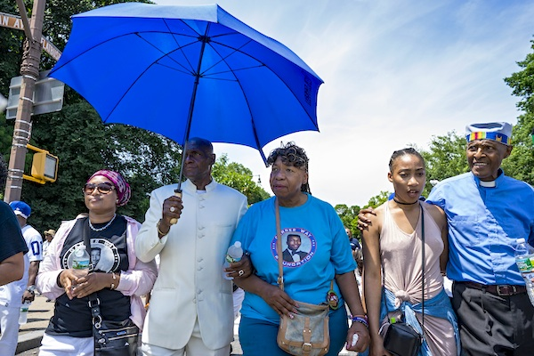 "Gwen Carr, mother of Eric Garner, center under umbrella, is joined by supporters as she and others march to a gathering in the Brooklyn borough of New York Saturday, July 16, 2016. Two years after the police chokehold death of Garner made ""I can't breath"" a rallying cry in the national protests about police killings of black men, federal prosecutors are still grappling with the question of whether to prosecute the white officer seen on videotape wrapping his arm around Garner's neck. (AP Photo/Craig Ruttle)"