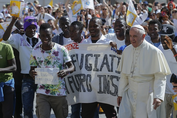 Pope Francis walks with a group of refugees he invited to join him on the steps of St. Peter's Basilica during his weekly general audience in St. Peter's Square at the Vatican, Wednesday, June 22, 2016. Francis begins a five-day visit to Poland on upcoming Wednesday July 27, 2016, and hopes to inspire aid to homeless strangers and acts of mercy for refugees during his visit, although Poland has closed its borders to refugees. (AP Photo/Fabio Frustaci,)