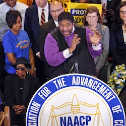 North Carolina NAACP president, Rev. William Barber, center at podium gesturing during a news conference in Richmond, Va. A federal appeals court on Friday, July 29, 2016, blocked a North Carolina law that required voters to produce photo identification and follow other rules disproportionately affecting minorities, finding that the law was intended to make it harder for blacks to vote in the presidential battleground state. Rev. Barber, said in an interview that the ruling was a powerful victory for civil rights and for democracy. (AP Photo/Steve Helber, File)