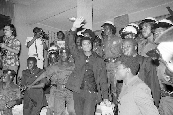 Heavyweight title challenger Muhammad Ali, surrounded by Zaire soldiers, waves to crowd upon his arrival in Kinshasa, Zaire on Sept. 11, 1974. Ali is in Zaire for a fight against George Foreman. Ali, the magnificent heavyweight champion whose fast fists and irrepressible personality transcended sports and captivated the world, has died according to a statement released by his family Friday, June 3, 2016. He was 74. (AP Photo/Horst Faas, File)