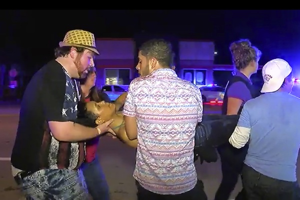 An injured person is escorted out of the Pulse nightclub after a shooting rampage, Sunday morning June 12, 2016, in Orlando, Fla. A gunman wielding an assault-type rifle and a handgun opened fire inside a crowded gay nightclub early Sunday, killing at least 50 people before dying in a gunfight with SWAT officers, police said. It was the deadliest mass shooting in American history. (AP Photo/Steven Fernandez)