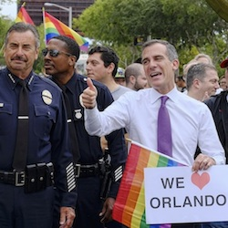 Los Angeles Mayor Eric Garcetti, center, flanked by Los Angeles Police Chief Charlie Beck, left, and Los Angeles World Airports Chief of Police Patrick M. Gannon, right, march in the gay pride parade in West Hollywood, Calif., on Sunday, June 12, 2016. Garcetti says a heavily armed man arrested in Southern California told police he was in the area for West Hollywood's gay pride parade. (AP Photo/Richard Vogel)