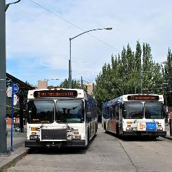 Two TriMet 2600-series buses (New Flyer D40LF buses built in 2002) at the main inbound bus stop at Rose Quarter Transit Center