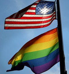 U.S. flag and pride flag flying at half-mast