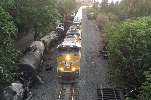 Crumpled oil tankers sits beside the railroad tracks after a fiery June 3 train derailment that prompted evacuations from the tiny Columbia River Gorge town of Mosier, Ore. Union Pacific announced Wednesday, June 22, 2016, plans to resume transporting oil by train through the Oregon side of the scenic Columbia River Gorge at some point this week. (Brent Foster via AP, File)
