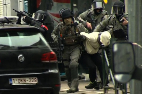 In this framegrab taken from VTM, armed police officers escort a suspect to a police vehicle during a raid in the Molenbeek neighborhood of Brussels, Belgium, Friday March 18, 2016. After an intense four-month manhunt across Europe and beyond, police on Friday captured Salah Abdeslam, the top fugitive in the Paris attacks in the same Brussels neighborhood where he grew up.