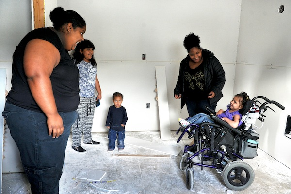 Amari Prewitt, right, smiles as her mom Elena Williams, left, sister Aniya Lopez, brother Julian Prewitt, and aunt Erica Williams show her the new bedroom she will be getting at their Habitat For Humanity House in Medford, Ore. (Denise Baratta /The Medford Mail Tribune via AP)