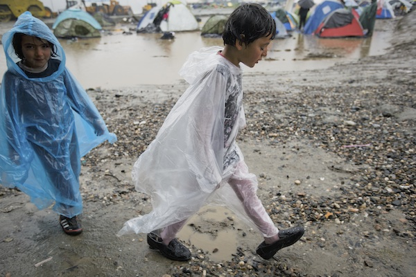 Children, one wearing adult sized shoes, walk next to large puddles at the northern Greek border station of Idomeni, Sunday, March 13, 2016. Bad weather returned after a brief pause and conditions in the refugee camp on the Greek-Macedonian where about 14,000 people are stranded have further deteriorated, many of its residents struggling struggling to cope with the many challenges posed by the heavy rain. (AP Photo/Vadim Ghirda)