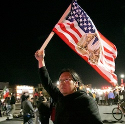 A protester holds a U.S. flag as hundreds gather in downtown Salt Lake City, where Republican presidential candidate Donald Trump held a campaign rally, Friday, March 18, 2016. (Benjamin Zack/Standard-Examiner via AP)