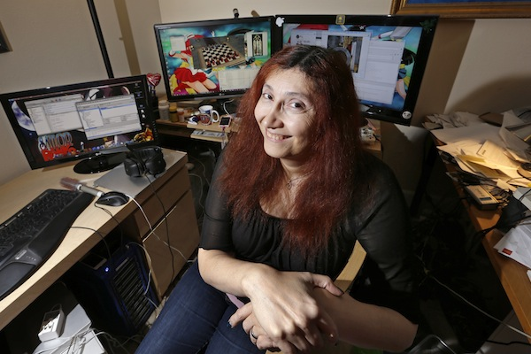 "longtime video game developer Becky Heineman poses for a photo at her workspace in Seattle. In the male-dominated world of multiplayer online games like ""Grand Theft Auto,"" ""Halo,"" and ""Call of Duty,"" many women say they've had to take drastic steps to escape harassment, stalking and violent threats from male players. Heineman, the founder of the Olde Skuul game studio in Seattle, used to be an aficionado of action-packed, violent games, but after being constantly harassed while playing highly-competitive games, she now plays simple, single-player games on her phone and computer. (AP Photo/Elaine Thompson)"