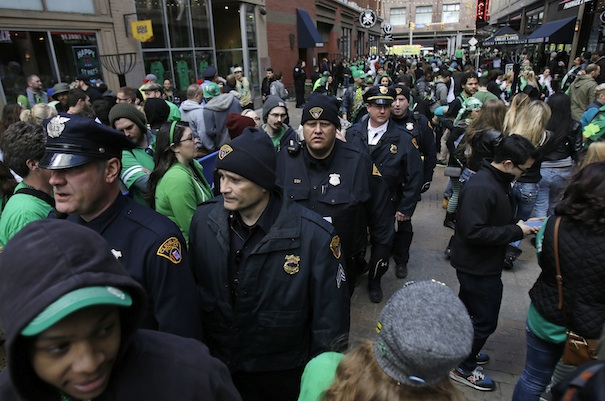 "arch 17, 2016 photo shows Cleveland Police walking with pedestrians as they patrol the area in downtown Cleveland. City officials have been coy about their plans for handling convention protests, saying only they are prepared for ""challenges"" and are working to free up jail cells, while activists have warily eyed the city's acquisition of riot gear. (AP Photo/Tony Dejak)"