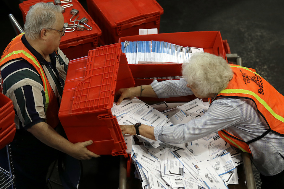 Election workers Louise Masog, right, and John Jones prepare ballots for counting at Multnomah County election headquarters for the primary election in Portland, Ore., May 17, 2016. Oregon's secretary of state says more than 2.5 million people are registered to vote for the first time in the state's history and predicted a record participation in the Nov. 8, 2016, election. The state is also on track to add over 250,000 new voters through the Oregon Motor Voter program in time for the election.(AP Photo/Don Ryan, File)