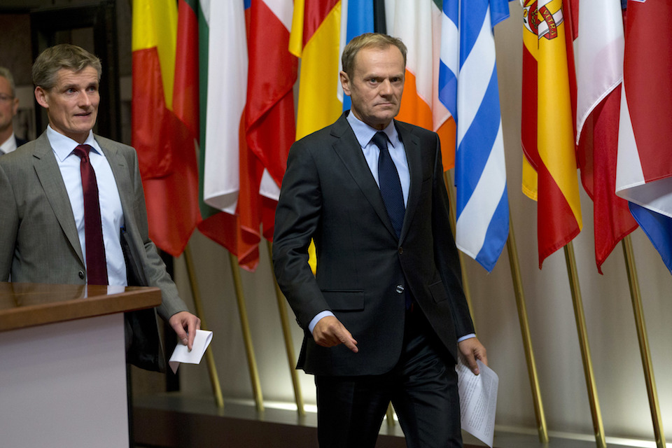 European Council President Donald Tusk walks by flags of EU nations prior to a media conference at the EU Council building in Brussels on Wednesday, Nov. 9, 2016. European Union leaders have invited President-elect Donald Trump to come visit the 28-nation bloc at his earliest convenience to assess trans-Atlantic ties. (AP Photo/Virginia Mayo)