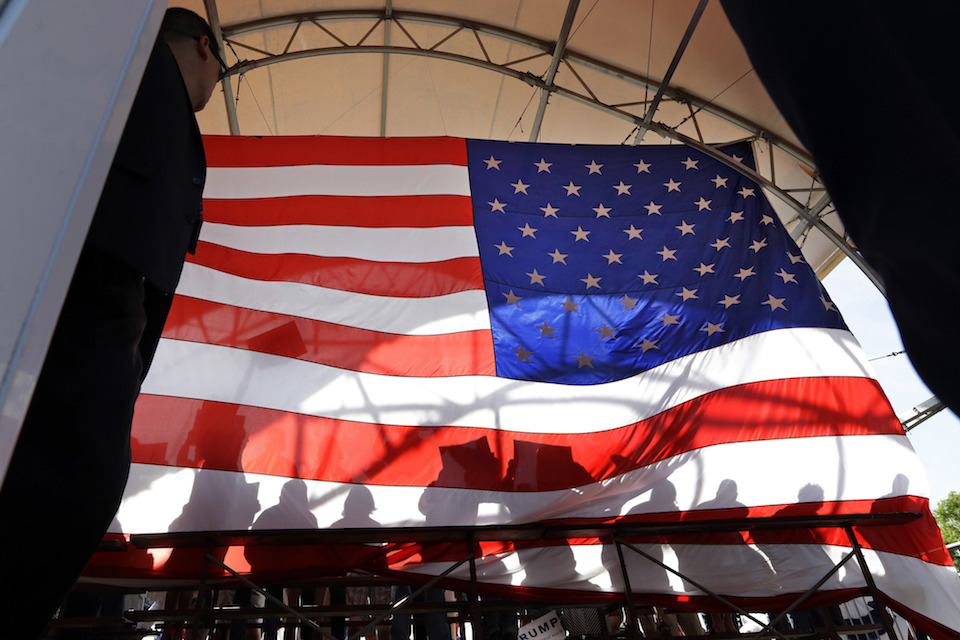 Shadows of people standing behind Republican presidential candidate Donald Trump on a large U.S. flag, viewed from backstage in Lynden, Wash., Saturday, May 7, 2016. In 2016, Americans are split over immigration, the changes wrought by globalization, the treatment of minorities and the threat of terrorism. But partisanship, long rising, has veered beyond policy disagreement. Now, roughly half of Democrats and Republicans tell pollsters they fear those in the other party. (AP Photo/Elaine Thompson)