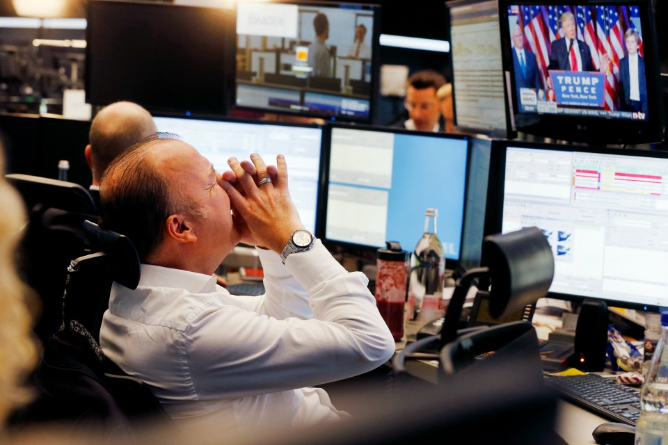A broker reacts as U.S. President-elect Donald Trump shows up on a television screen at the stock market