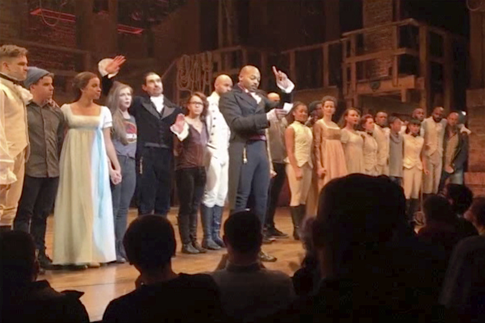 "Image made from a video provided by Hamilton LLC, actor Brandon Victor Dixon who plays Aaron Burr, the nation's third vice president, in ""Hamilton"" speaks from the stage after the curtain call in New York, Friday, Nov. 18, 2016. Vice President-elect Mike Pence is the latest celebrity to attend the Broadway hit ""Hamilton,"" but the first to get a sharp message from a cast member from the stage. (Hamilton LLC via AP)"