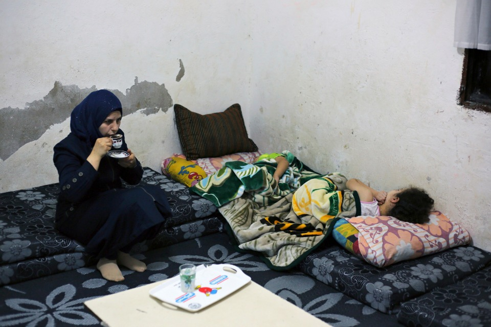 Syrian refugee Haela Kalawi, 31, whose husband is missing in Syria, drinks coffee as she sits beside her sleeping children at their home in Ouzai, a poor neighborhood in the Lebanese capital of Beirut